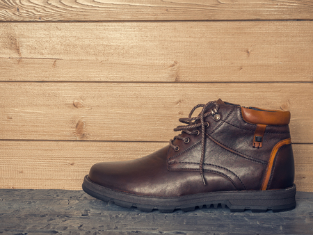 Classic mens boot with his left foot on the wooden floor near the wall.