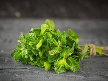 A bundle of fresh cut mint on a dark rustic table. The concept of healthy eating. The use of herbs.