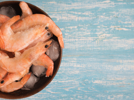 Frozen prawns in a clay bowl with ice on a wooden table. The view from the top.