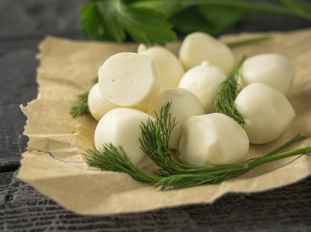 Freshly made balls of mozzarella cheese in the wrapping paper on a rustic table. Rustic food from natural products.