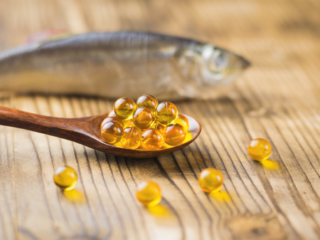 Fish oil capsules in a wooden spoon on a wooden table with a fish in the background. Selective focus. Traditional medicine.