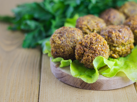 Freshly made falafel on a salad leaf on a cutting Board on a dark wooden table. Eastern vegetarian meal of chickpea.