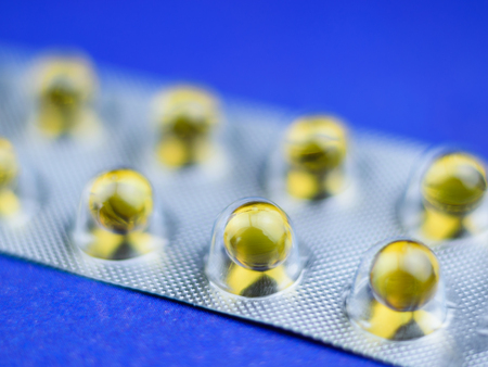 Fish oil pills in a blister selective focus. Background of medicines.
