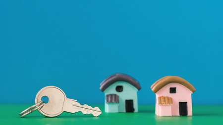 Ceramic model of a house and key on color table. Selective focus.