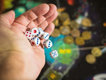 Male hand throwing dice on the playing field with money. The concept of gambling. Business still life.