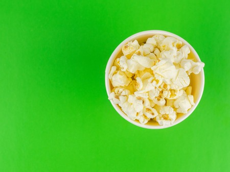 Paper popcorn Cup on a green background. Place for your text. Reklamní fotografie