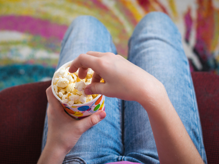 Baby in a chair on a colorful background with a bowl of popcorn. The concept of partying and watching of movies. Stock Photo