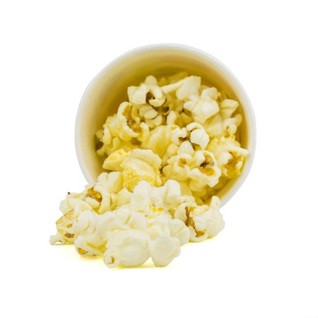 The popcorn is poured from a paper Cup isolated on a white background. The concept of partying and watching of movies.