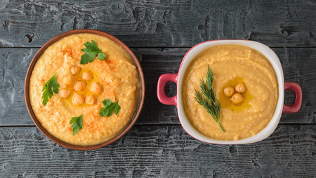 Two bowls with fresh hummus on a wooden table. Vegetarian middle Eastern dish and chickpea. The view from the top. Stock Photo