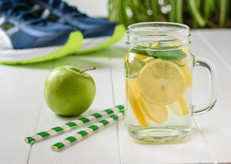 A mug of lemon and mint and two cocktail tubes with sneakers in the background. The concept of a healthy lifestyle. Bottle for sports.