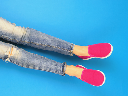 Legs of the girl with a broken knee in torn jeans on the blue floor. The view from the top. The concept of modern sports style.