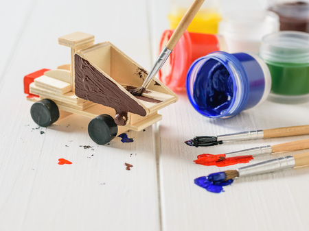 The process of coloring the machine with colorful gouache on a white wooden table. Creative kit. Hobby and style. Stockfoto