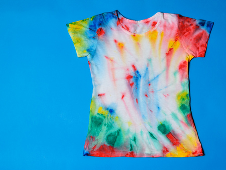 T-shirt painted in tie dye style on a blue background. White clothes painted by hand. Flat lay. Place for text. Фото со стока
