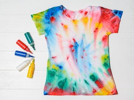 Tubos de pintura para ropa y camiseta en estilo tie dye sobre una mesa de madera blanca. Ropa blanca pintada a mano. Endecha plana.