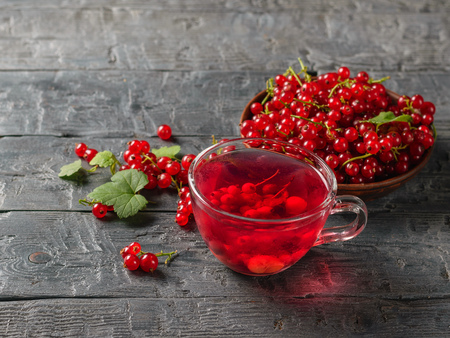 Therapeutic drink of red currant berries and fresh berries on the village table. Refreshing natural drink. The concept of healthy natural food. Stock Photo