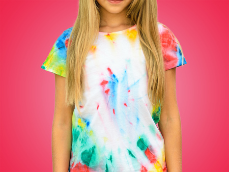 Girl in a t-shirt in the style of tie dye on a red background. White clothes painted by hand. Banque d'images