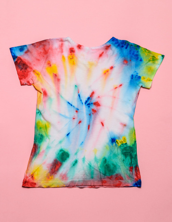 Reverse side of tie dye style t-shirt on pink background. White clothes painted by hand. Flat lay. Place for text. Pastel color.