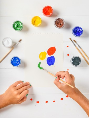 The child selects the desired color on a white wooden table. Creative kit. Hobby and style.