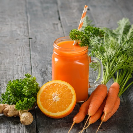 A mug of fresh carrot smoothie with cocktail straw, parsley, ginger root and oranges on a dark wooden table. The concept of healthy eating.