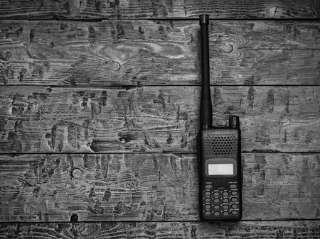 Schwarz-Weiß-Bild eines Walkie-Talkies auf einem Holztisch. Drahtlose Kommunikationseinrichtung der Vergangenheit.