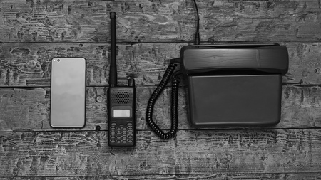 Black and white image of a walkie-talkie on a wooden table. Wireless communication facility of the past.