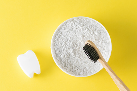 A jar of tooth cleaning powder, a wooden toothbrush and a tooth figurine on a yellow table. Oral care products. The view from the top. Flat lay.