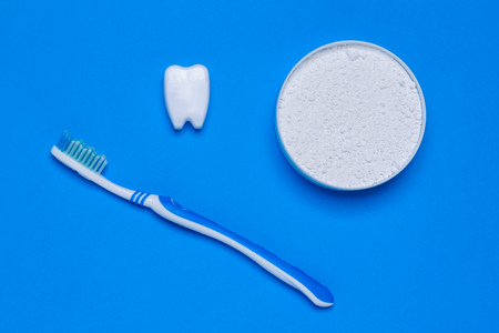 A jar of tooth cleaning powder, a blue toothbrush and a tooth figurine on a blue table. Oral care products. The view from the top. Flat lay. 写真素材