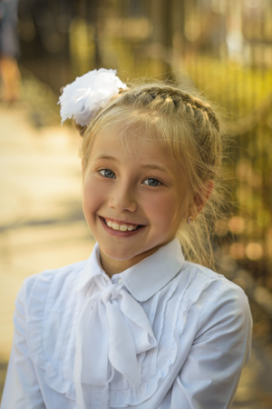 A beautiful girl with a white bow on her head laughs cheerfully before going to school. Portrait of a school-age child playing in the autumn Park. Stok Fotoğraf