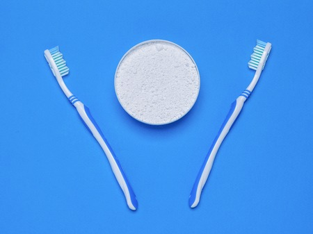 Two toothbrushes and a jar of tooth powder on the blue table. Oral care products. The view from the top. Flat lay. Banque d'images