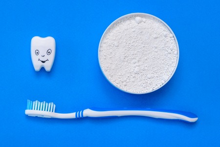 The tooth figurine smiles next to the tooth powder and toothbrush. Oral care products. The view from the top. Flat lay. 写真素材