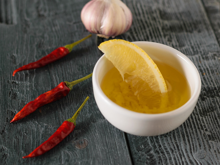 Olive oil with garlic and lemon in a white bowl on a dark table. Dressing for diet salad. Vegetarian food.
