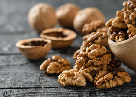 Peeled walnuts are poured from a wooden bowl onto a dark wooden table. Natural and dietary food.