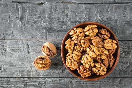 Split walnuts in a clay Cup on a wooden rustic black table. Natural and dietary food. The view from the top. Flat lay.