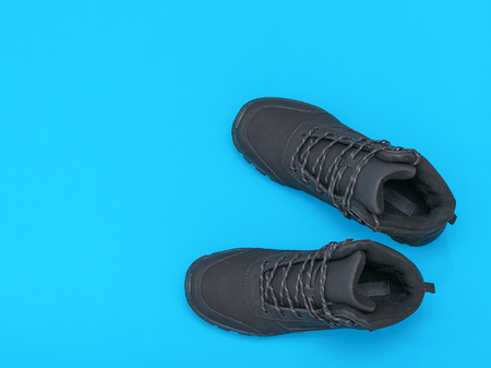 Insulated black casual men's shoes on blue and blue background. Men's shoes for cold weather. Casual sports men's shoes. Flat lay. The view from the top.