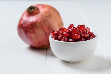 Seeds of ripe pomegranate in white Cup on white wooden table. Harvest ripe pomegranate . Vegetarian food. Raw food. Reklamní fotografie