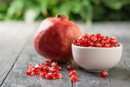 White Cup with pomegranate seeds and ripe pomegranate on black wooden table. Harvest ripe pomegranate . Vegetarian food. Raw food.
