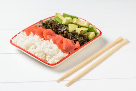 A plate of Hawaiian rice, avocado, salmon, and kelp. Mediterranean diet cuisine