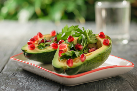 A glass of clean water with avocado halves filled with pomegranate seeds and herbs. Vegetarian cuisine for weight loss. Healthy diet.
