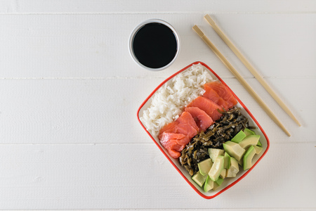 Bowl with long-grain rice, seaweed, avocado slices, salmon and wooden sticks on a white wooden table. Mediterranean diet cuisine. The view from the top. Flat lay.