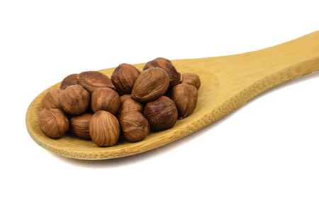 Large wooden spoon with hazelnuts isolated on white background. Natural diet vegetarian food.