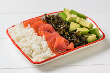 Bowl with rice, avocado, salmon and kelp on a white wooden rustic table. Mediterranean diet cuisine