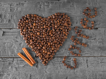A heart of coffee beans and two cinnamon sticks on a black wooden table. The view from the top. Flat lay. Grains for the preparation of the popular drink.