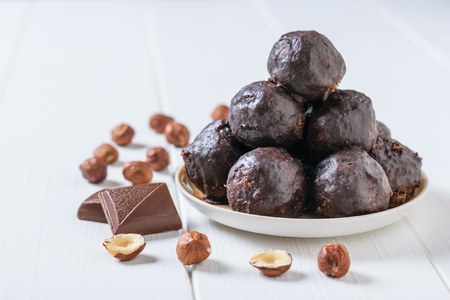 Hand-made balls of dried fruits, nuts and chocolate on a white wooden table. Delicious fresh home-made candies. 写真素材