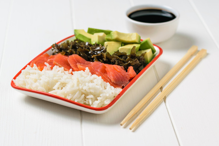 Bowl with soy sauce and salad of avocado, rice, seaweed and fish on white table. Mediterranean diet cuisine 스톡 콘텐츠