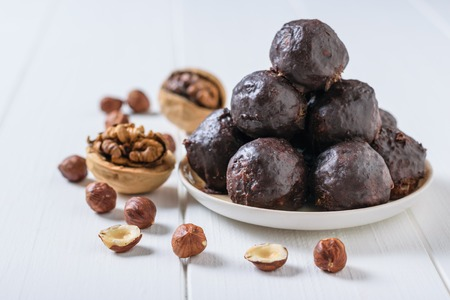 Chocolate-drenched balls of grated nuts and dried fruits in a bowl on a white wooden table. Delicious fresh home-made candies.