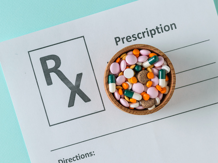 Wooden bowl filled with colorful tablets on the form with the appointment of a doctor. The view from the top. The concept of treatment and prevention of diseases. Flat lay.