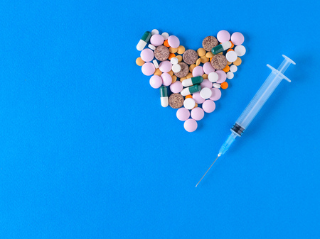 Heart of colored pills and syringe on blue background. The view from the top. The concept of treatment and prevention of diseases. Flat lay. Stock Photo