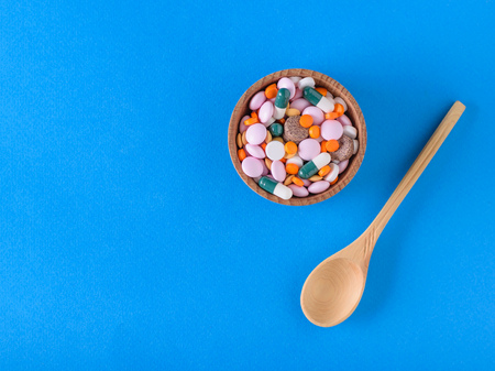 Wooden spoon beside the wooden bowl of pills on a blue background. The view from the top. The concept of treatment and prevention of diseases. Flat lay. Stock Photo
