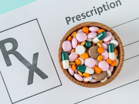 A sheet with a doctors prescription and a wooden bowl with pills on a blue table. The view from the top. The concept of treatment and prevention of diseases. Flat lay. Stock Photo