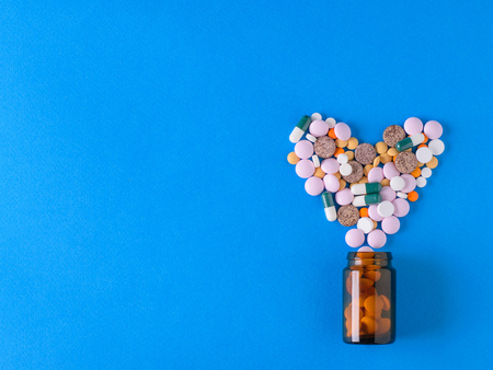 Multicolored heart-shaped pills pour out of a glass brown bubble on a blue background. The view from the top. The concept of treatment and prevention of diseases. Flat lay.